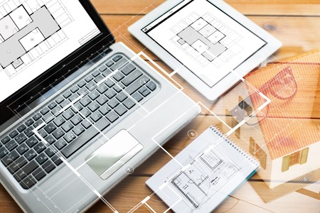 architectural studies: architecture, business and technology concept - close up of on laptop computer, tablet pc, notebook and eyeglasses with blueprint of room on wooden table