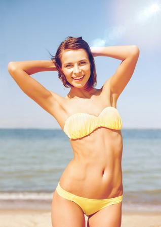 vacaciones en la playa: vacaciones de verano, vacaciones y concepto de la playa - chica posando en bikini en la playa Foto de archivo