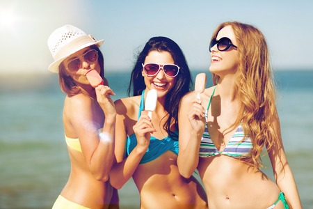 summer holidays and vacation - girls in bikini with ice cream on the beach