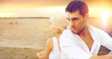 breaking up: summer holidays and dating concept - couple sitting at sea side Stock Photo