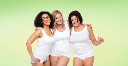 cheerful: friendship, beauty, body positive and people concept - group of happy plus size women in white underwear over green natural background