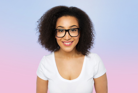 negras africanas: anuncio, la educación, el origen étnico, la visión y el concepto de la gente - Mujer africana joven sonriente en gafas y camiseta blanca más de cuarzo rosa y blanco gradiente de la serenidad