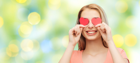 facial expression: love, romance, valentines day and people concept - smiling young woman or teenage girl with red heart shapes on eyes over summer green lights background