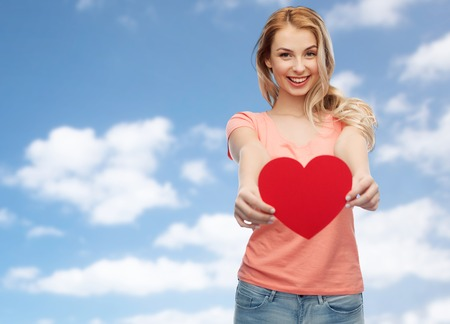 romance sky: love, romance, charity, valentines day and people concept - smiling young woman or teenage girl with blank red heart shape over blue sky and clouds background