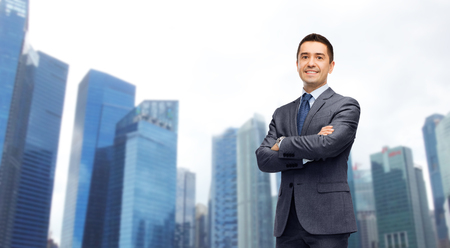 business, people and office concept - happy smiling businessman in dark grey suit over singapore city skyscrapers background
