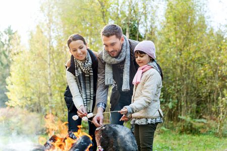 roasting: camping, travel, tourism, hike and people concept - happy family roasting marshmallow over campfire Stock Photo