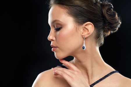 beauty, jewelry, people and luxury concept - close up of beautiful young asian woman with earring over black background
