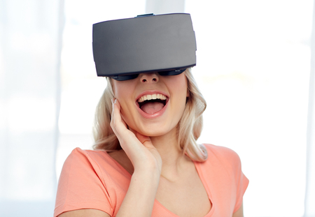 mediated: technology, virtual reality, cyberspace, entertainment and people concept - happy amazed young woman with virtual reality headset or 3d glasses at home