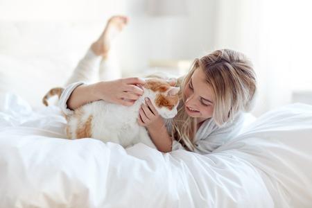 mujer en la cama: animales domésticos, por la mañana, la comodidad, el descanso y el concepto de la gente - mujer joven feliz con el gato en cama en su casa