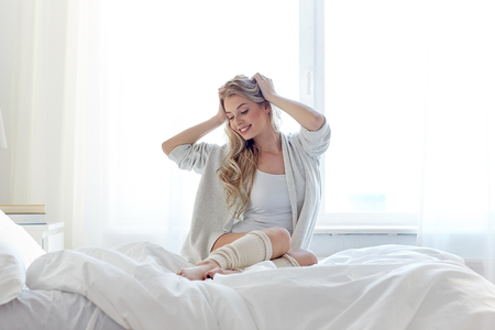 legwarmers: rest, sleeping, comfort and people concept - happy young woman stretching in bed at home bedroom