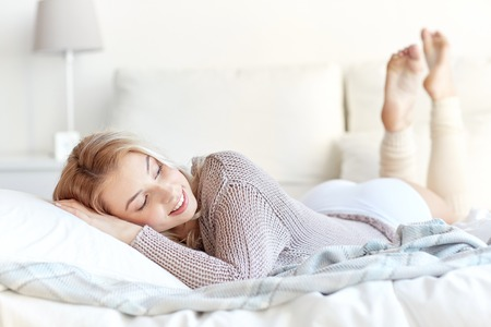 Rusten, slapen, comfort en mensen concept - happy jonge vrouw in bed lag thuis slaapkamer Stockfoto - 62353792