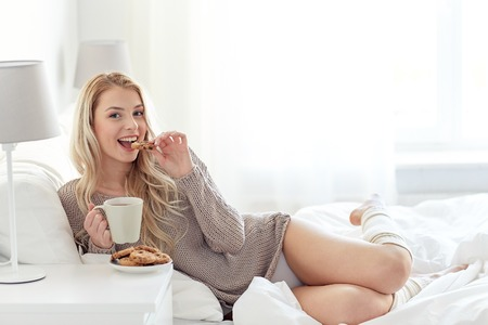 women coffee: morning, leisure and people concept - happy young woman with cup of coffee or tea eating cookie in bed at home bedroom