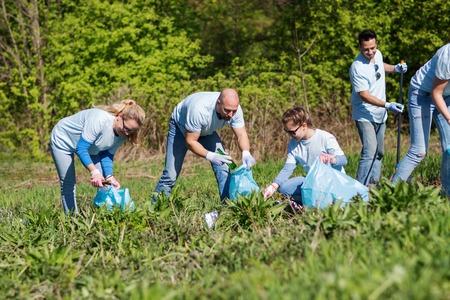Freiwilliges Engagement, Charity, Reinigung, Menschen und Ökologie-Konzept - Gruppe von glücklichen Freiwilligen mit Müllsäcken Bereich im Park Reinigung Standard-Bild - 62353804