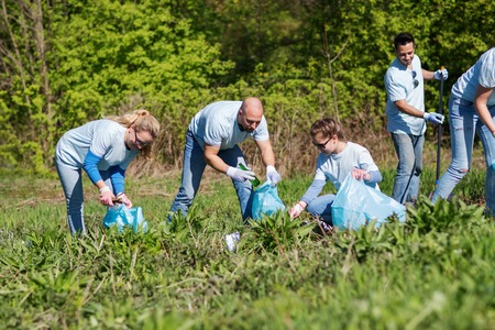 volunteering, charity, cleaning, people and ecology concept - group of happy volunteers with garbage bags cleaning area in park Reklamní fotografie - 62353804