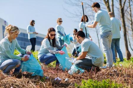 el voluntariado, la caridad, la limpieza, la gente y el concepto de ecología - grupo de voluntarios felices con bolsas de basura área de limpieza en el parque Foto de archivo