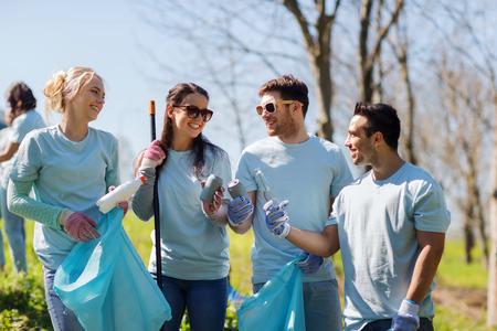 basura: el voluntariado, la caridad, la limpieza, la gente y el concepto de ecología - grupo de voluntarios felices con bolsas de basura de limpieza zona del parque de las latas y botellas viejas Foto de archivo