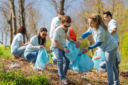 charity work: volunteering, charity, cleaning, people and ecology concept - group of happy volunteers with garbage bags cleaning area in park
