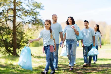 ボランティア、チャリティー、クリーニング、人々 とエコロジー コンセプト - ゴミ袋公園を歩いて幸せなボランティアのグループ