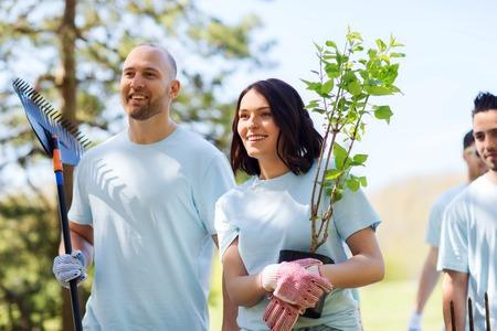 community garden: volunteering, charity, people and ecology concept - group of happy volunteers with tree seedlings and rake walking in park