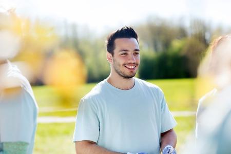 selfless: volunteering, charity, people, teamwork and environment concept - happy volunteer man in park