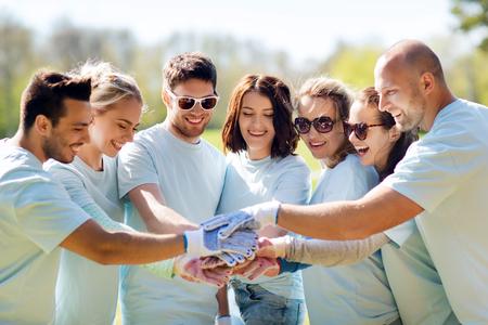 자원 봉사, 자선, 사람, 제스처 및 생태 개념 - 공원에서 위에 손을 퍼 팅하는 행복 한 자원 봉사자의 그룹
