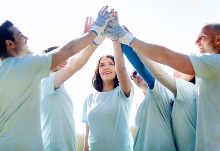 ボランティア、慈善団体、人々、ジェスチャー、エコロジー コンセプト - 公園でハイタッチを作る幸せなボランティアのグループ