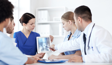 group meeting: profession, people, surgery, radiology and medicine concept - group of doctors with x-ray on tablet pc computer screen meeting at medical office Stock Photo