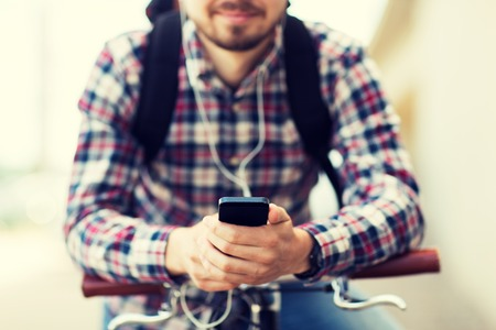 people, travel, technology, leisure and lifestyle - close up of young hipster man in earphones with smartphone and fixed gear bike listening to music on city street Stock Photo - 62353877