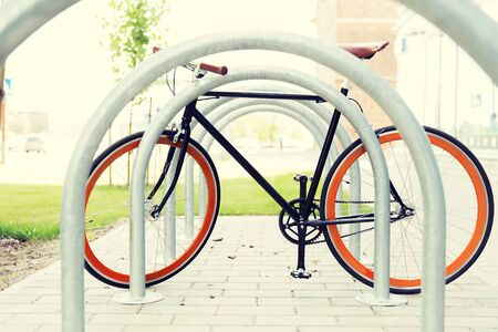 fixed: transport, storage and vehicle concept - close up of fixed gear bicycle at street parking outdoors Stock Photo
