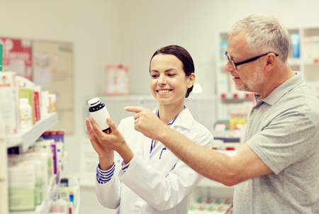 la medicina, la farmacia, la atención de la salud y la gente concepto - farmacéutico feliz mostrando medicamento para el cliente hombre mayor en farmacia