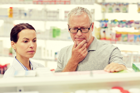 finding the cure: medicine, pharmaceutics, health care and people concept - pharmacist showing drug to senior man customer at drugstore