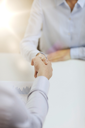 modern businesswoman: business and office concept - businesswoman and businessman shaking hands in office