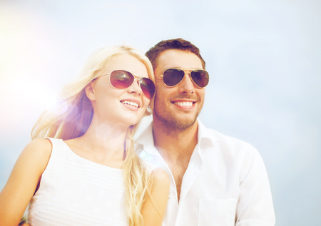summer holidays and dating concept - happy couple in sunglasses over blue sky background Stock Photo