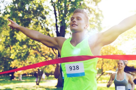 sporting event: fitness, sport, victory, success and healthy lifestyle concept - happy man winning race and coming first to finish red ribbon over group of sportsmen running marathon with badge numbers outdoors Stock Photo