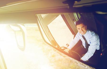 chofer: el transporte, el transporte, el turismo, viaje por carretera y la gente concepto - primer plano de la sonrisa reflejo en el espejo del conductor del autobús de pasajeros