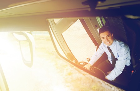 transport, transportation, tourism, road trip and people concept - close up of smiling driver reflection in passenger bus mirror Stock Photo