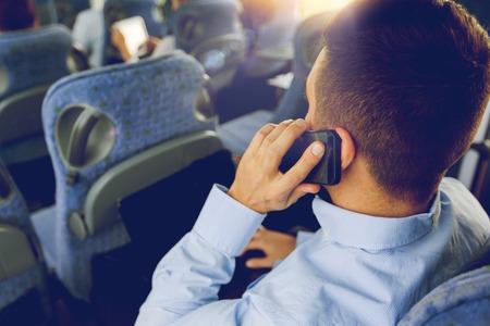 transporte, turismo, viajes de negocios y la gente concepto - cerca del hombre con el teléfono inteligente y un ordenador portátil que llama en autobús viajes Foto de archivo