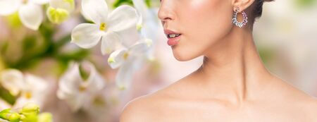 natural beauty: glamour, beauty, jewelry and luxury concept - close up of beautiful woman face with earring over natural spring lilac blossom background
