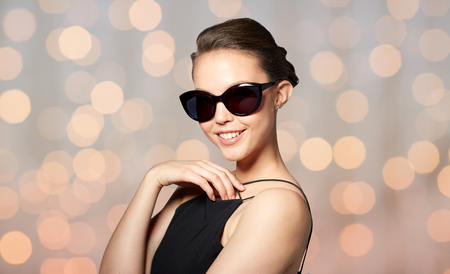 eyewear fashion: accessories, eyewear, fashion, people and luxury concept - smiling beautiful young woman in elegant black sunglasses over holidays lights background
