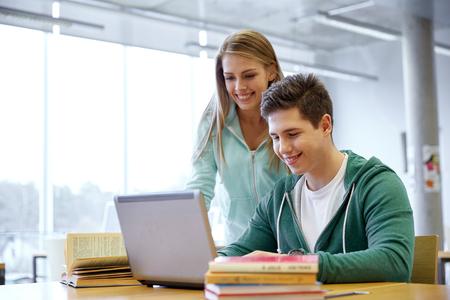 Bildung, Menschen, Technologie und Lernkonzept - glücklich High-School-Studenten mit Laptop-Computer im Klassenzimmer oder Bibliothek Standard-Bild - 62353988