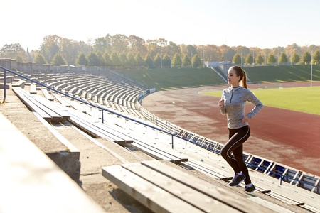 tracksuit: fitness, sport, exercising and people concept - happy young woman running upstairs on stadium