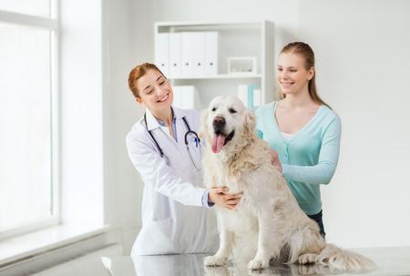 mujer perro: medicina, mascotas, animales, cuidado de la salud y la gente concepto - mujer feliz con el perro perdiguero de oro y el médico veterinario en la clínica veterinaria