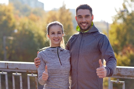 approvement: fitness, sport, people, gesture and lifestyle concept - smiling couple outdoors showing thumbs up at city