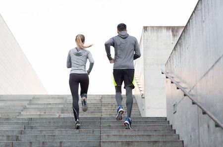 Fitness, deporte, personas, ejercicio y estilo de vida concepto - pareja corriendo arriba escaleras de la ciudad Foto de archivo