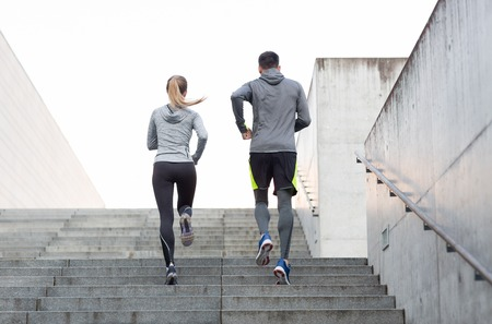 upstairs: fitness, sport, people, exercising and lifestyle concept - couple running upstairs on city stairs