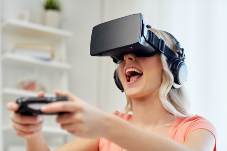 3d technology, virtual reality, gaming, entertainment and people concept - happy young woman in virtual reality headset or 3d glasses and headphones playing video game with controller gamepad at home