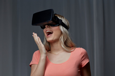 futuristic girl: technology, virtual reality, cyberspace, entertainment and people concept - happy amazed young woman with virtual reality headset or 3d glasses at home