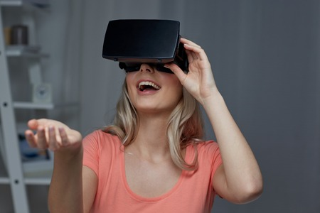 mediated: technology, virtual reality, entertainment and people concept - happy young woman with virtual reality headset or 3d glasses playing game at home and holding something invisible Stock Photo