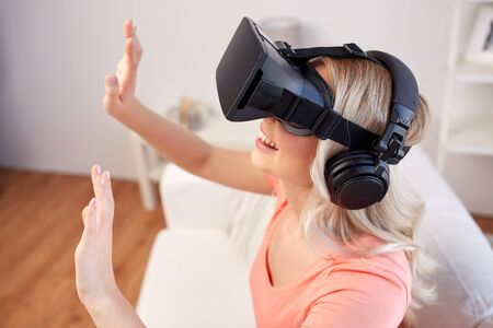 mediated: technology, virtual reality, entertainment and people concept - happy young woman in virtual reality headset or 3d glasses and headphones playing game at home and touching something invisible