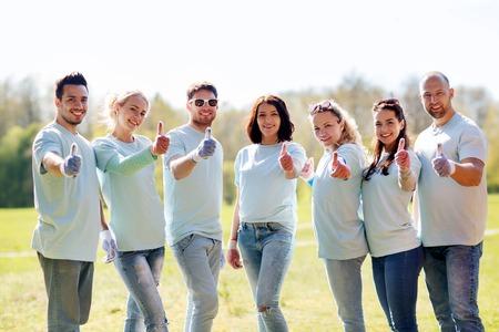 자원 봉사, 자선, 사람, 제스처 및 생태 개념 - 공원에서 엄지 손가락을 보여주는 행복 한 자원 봉사자의 그룹